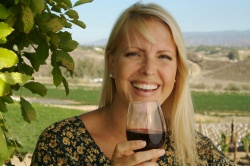 Beautiful woman smiling as she is wine tasting on a summer day.