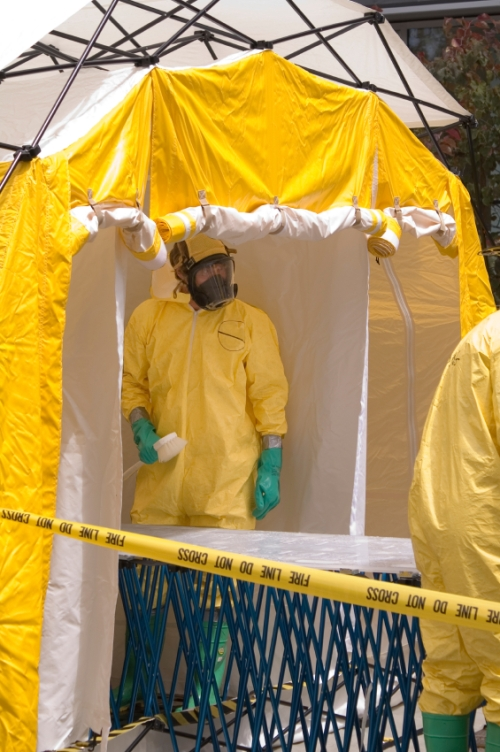 Hazmat-suited healthcare worker in a decontamination shower